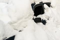 Abandoned snow covered car with an open window is totally obscured by a mass  Stock Photos
