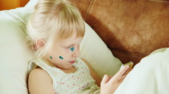 Sick child playing on the phone. Her face in the green points Stock Footage