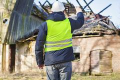 Building inspector filming on tablet PC burned barn roof - stock photo