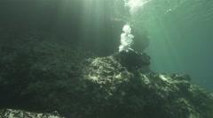 Diver swim around underwater reef spectacular illuminated by sunlight Stock Footage
