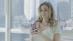 Blonde woman indoor urban 4K happy in toronto surfing online mobile social media Stock Footage