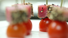 Tuna with cherry tomatoes on a skewer with sesame seeds. Cold appetizer - stock footage