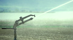 Irrigating system spraying water in a field of close in slow motion Stock Footage