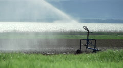 Irrigating system spraying water in the field in slow motion Stock Footage