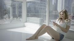 Blonde woman indoor urban scene in 4K relax online with mobile device Stock Footage