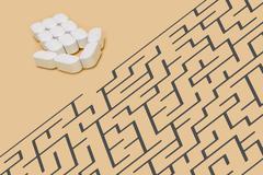 Arrow of Pills along with a labyrinth on brown background - stock photo