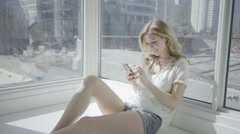 Blonde woman sitting in her condo using phone for social media in 4K Stock Footage