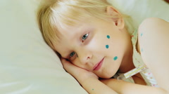 Girl 4-5 years lying on a bed, it measures the temperature with a thermometer Stock Footage