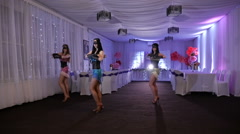 Three beautiful girls in masks dancing in a white room. The dress is decorated Stock Footage