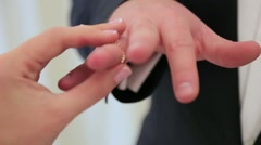 Bride wears on the groom's finger a wedding wear close up - stock footage