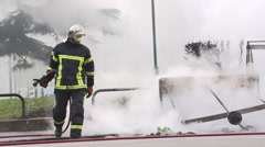 Firefighter extinguishing fire Stock Footage