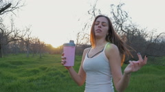 Young beautiful woman drinking water after sport in park at sunset, slow motion - stock footage