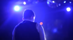 Host of the show standing on a brightly lit stage rear view - stock footage