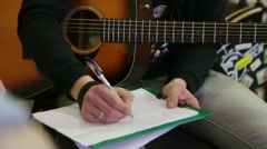 Guy with an acoustic guitar writes chords on a sheet Stock Footage