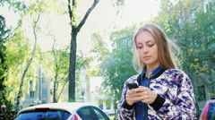 Attractive woman walking in the city, enjoys a smartphone. The sun's rays fall Stock Footage