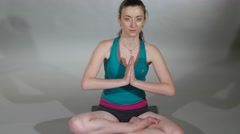 Young woman performs the lotus position and then folds hands for namaste Stock Footage