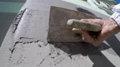 Close-up workers hand with trowel plastering the wall slow motion Stock Footage