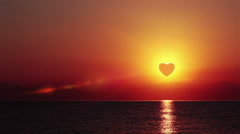 The sun in heart shape rising over the sea- timelapse Stock Footage