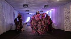 Three beautiful girls dance gypsy dance in costume in the white room Stock Footage