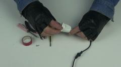 Man wearing black gloves fixing electrical plug Stock Footage