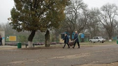 Several Women Carry Leaves on Cloth Through Main Gate of Zoo Stock Footage