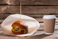 Hamburger and paper coffee cup. Stock Photos