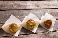 Burgers on white wrappers. Stock Photos