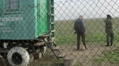 Puppy Running Around Guards About Supply Room on Wheels View Through Chain-Link Stock Footage