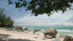 Water laps against sand on rocky, tropical beach. Thailand, Phuket - stock footage