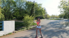 Attractive young woman rollerblading in part in the morning and smiling - stock footage