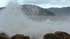 Breakers Crash over a Rocky Beach on a Cloudy Day. UltraHD video - stock footage