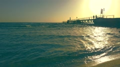 Silhouettes of people on the jetty at dawn Stock Footage
