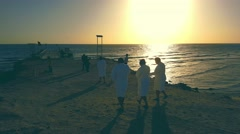 Silhouettes of people on the beach near the pier by the sea at dawn Stock Footage