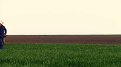Two middle age farmers in a field of wheat during fertilizer spreading. - stock footage