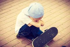 Lonely sad child with skateboard. Loneliness. - stock photo