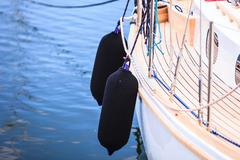 Side of hull sailboat with black fenders - stock photo
