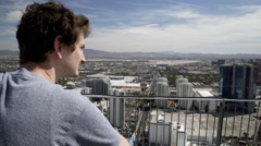 man looking over the guard railing of the stratosphere hotel in las vegas 4k - stock footage