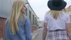 Young Women Walk Down Cool Urban Industrial Alley, Backs To Camera Stock Footage