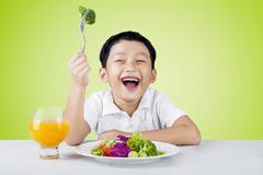 Child eat salad and drink orange juice - stock photo