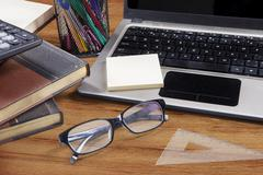 Laptop with glasses and stationery - stock photo