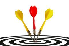 Three darts hitting the middle of dartboard Stock Photos