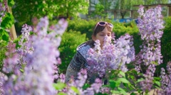 Girl smelling lilac Bush  Stock Footage