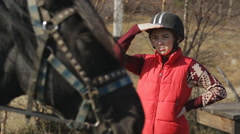 The woman jockey is looking into horse standing next to the domestic hoofed - stock footage