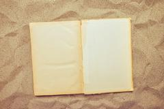 Top view of vintage open book on sandy beach Stock Photos