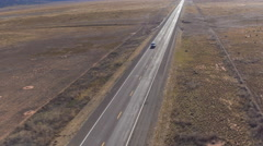 AERIAL: SUV car driving along the empty countryside road in sunny summer Stock Footage
