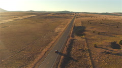 AERIAL: Flying above SUV car driving along empty countryside road at sunset Arkistovideo