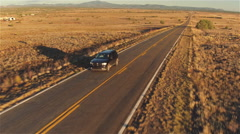AERIAL: SUV car driving along empty countryside road at sunset Stock Footage