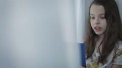 Beautiful little girl learns a poem by window Stock Footage