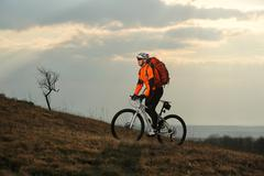 Man cyclist with backpack riding the bicycle Stock Photos