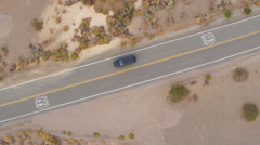 AERIAL: Black SUV car on road trip driving along the historic Route 66 in USA Stock Footage